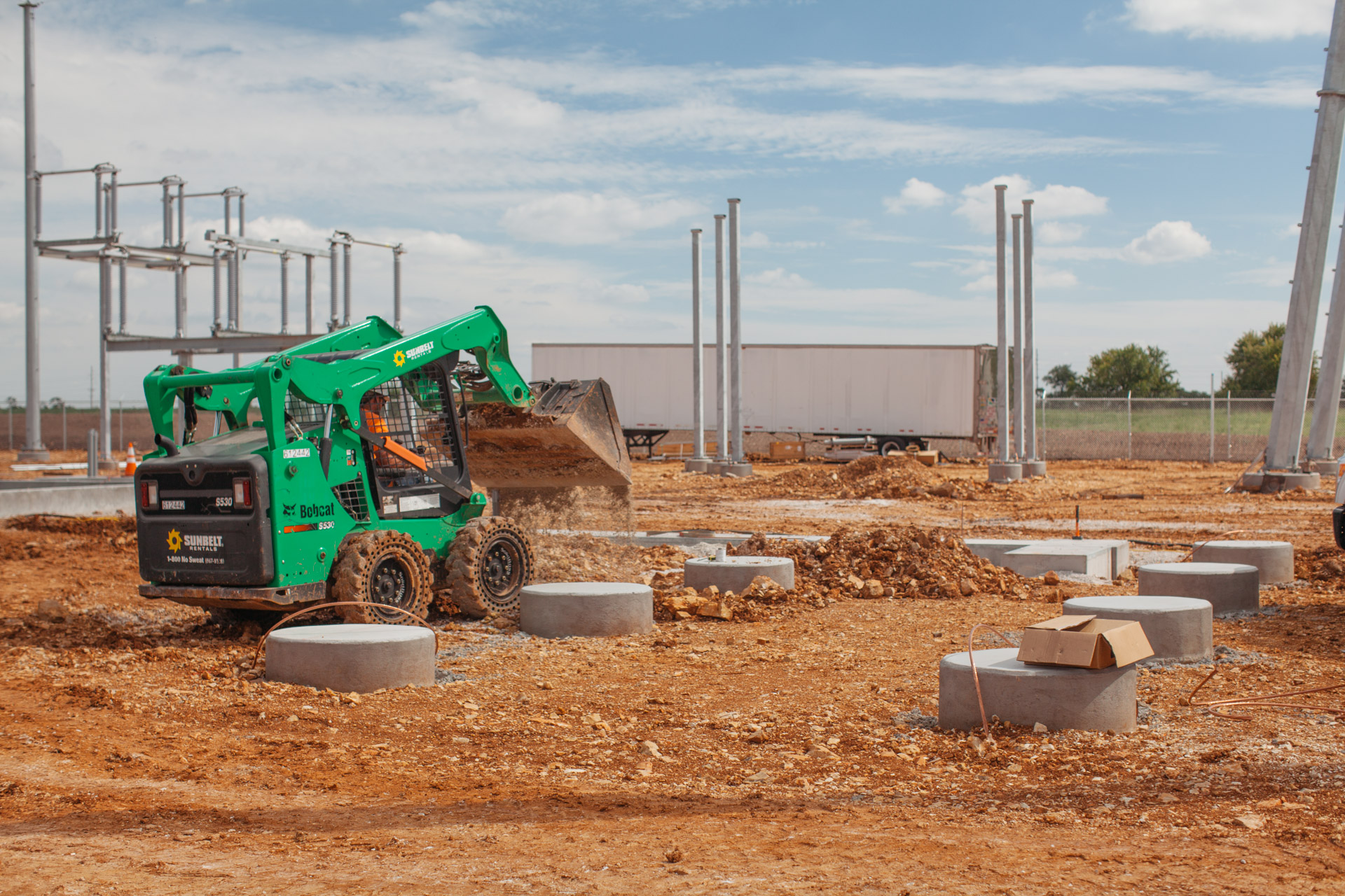 Image of small bulldozer dumping a load of dirt at the Empire Substation construction site in Joplin, MO.
