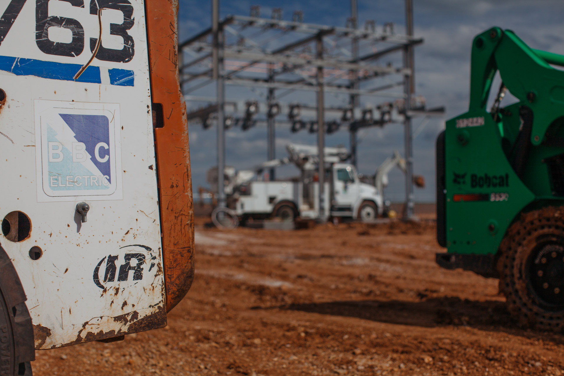 Image of closeup of BBC Electric truck with Joplin, MO's Empire Substation construction site in background.